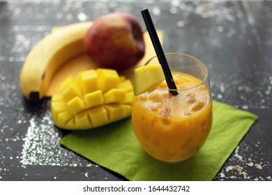 delicious smoothie with mango in a glass with crushed ice and straw Fresh fruit in the background