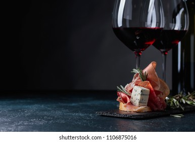 Delicious snack and glasses of red wine. Sandwich with prosciutto, blue cheese and rosemary on a dark background.  Copy space for your text.