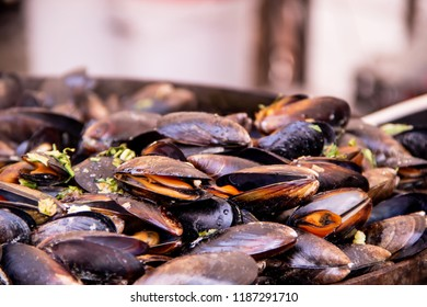 Delicious snack for gourmands with mussels in a large frying pan, street food