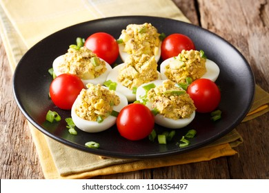 Delicious snack: stuffed eggs with tuna, avocado served with tomatoes and green onions close-up on a black plate on the table. horizontal