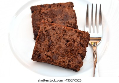 Delicious and soft fresh homemade brownie chocolate, square and sliced on white dish