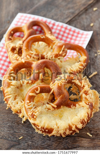 Delicious soft pretzels with cheese on a wooden background