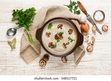Delicious soup puree with champignons in a pot surrounded by scattered fresh mushrooms and ingredients on a rustic wooden table.