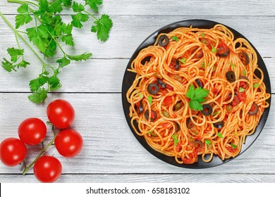 Delicious Spaghetti alla puttanesca with capers. olives, anchovies, tomato sauce sprinkled with parsley on black plate on wooden table, authentic basic recipe, view from abov