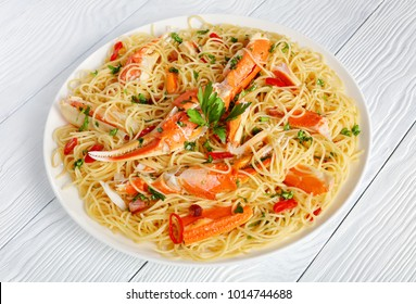 delicious spaghetti with cracked Crab in Spicy White Wine Sauce, sprinkled with finely chopped parsley and red chile on white plate, view from above, close-up
