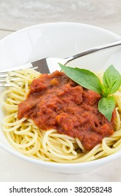 Delicious spaghetti pasta dinner in bowl garnished with three basil leaves, napkin and fork on top over wooden table