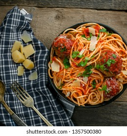 Delicious spaghetti pasta with meatballs and tomato sauce in a bowl. Traditional American Italian food on a rustic wooden table. Top view shot.