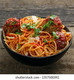 Delicious spaghetti pasta with meatballs and tomato sauce in a bowl. Traditional American Italian food on a rustic wooden table.