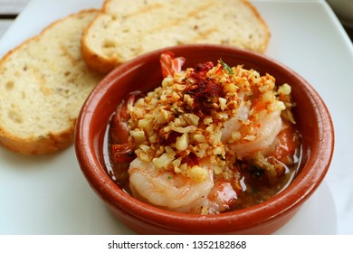 Delicious Spanish Style Garlic Shrimp or Gambas al Ajillo with Blurry Sliced Breads in Background