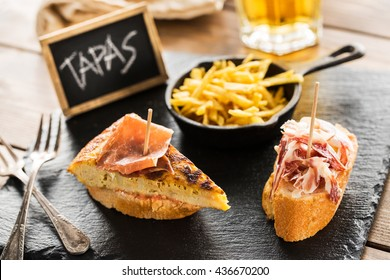 Delicious spanish tapas and beer served on a wooden table.