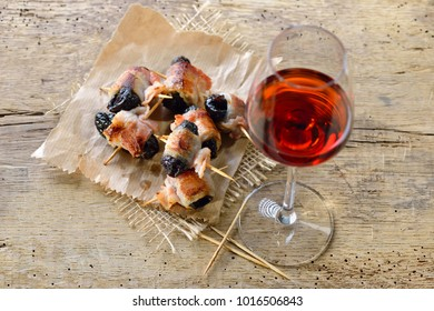 Delicious Spanish tapas:  Fried prunes wrapped in bacon served with Portuguese port wine