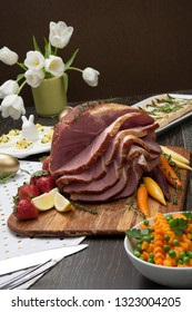 Delicious spicey roasted ham with deviled eggs, asparagus parmesan pastry, butternut squash with green peas, baby carrots, strawberries, and Easter decoration.