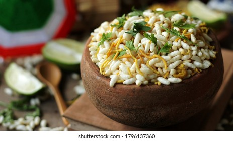 delicious, spicy Bengali snacks, Jhalmuri, is served in an earthen bowl placed on a wooden table with other ingredients like lemon being spread around it.