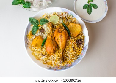 Delicious spicy chicken biryani in white bowl on white background, Indian or Pakistani food.