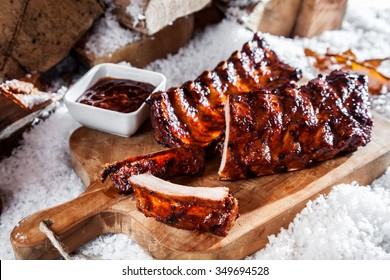 Delicious spicy grilled winter spare ribs fresh from the barbecue served on a wooden board outdoors in the snow