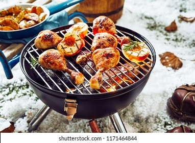Delicious spicy marinated chicken legs grilling over winter barbecue outdoors in snow with fresh fruit accompaniments