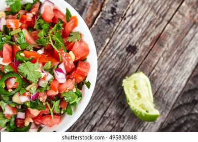 Delicious, spicy sauce Pico de Gallo also called salsa Fresca. Traditional recipe, fresh tomatoes, red onion, cilantro, lime juice and spicy jalapenos. National Mexican cuisine. Top view
