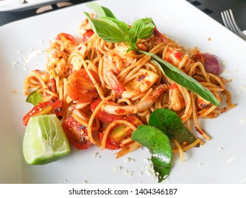 Delicious spicy tomyam spaghetti with shrimp squid and Thai spices on white plate in Thai fusion food restaurant.