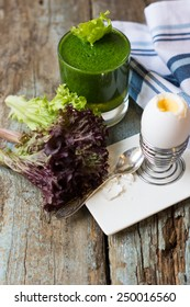 Delicious spinach smoothie and boiled eggs on the wooden table