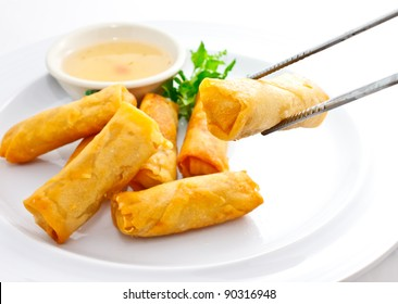 delicious springrolls with sweet plum sauce, one piece is held by chopstick