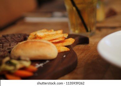 Delicious steak and fries. Wooden table presentation with bread and garnish. steak house restaurant table presentation.