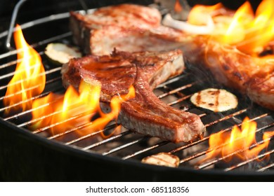 Delicious steak on grilling grid and flame, closeup