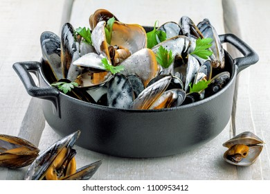 Delicious Steamed Mussels With Wine And Cream on a table. French meal Moules marinière in a bowl. Close-up shot.