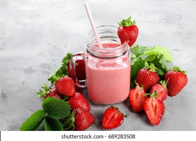 Delicious strawberry homemade smoothie in mason jar on grey background