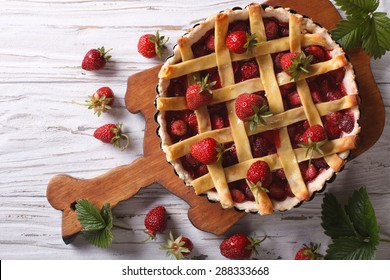 delicious strawberry pie in the baking dish on the table. vertical view above, rustic style