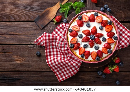 Delicious strawberry pie with fresh blueberry and whipped cream on wooden rustic table, cheesecake, top view