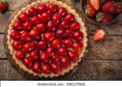 delicious strawberry tart on wooden background, top view