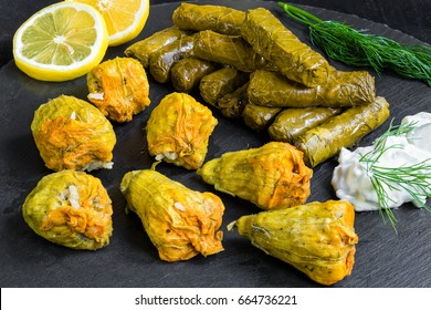 Delicious stuffed grape leaves and squash blossoms (the traditional dolma of the mediterranean cuisine) on black dish with tzatziki sauce, lemon slices and dill