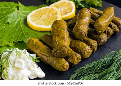Delicious stuffed grape leaves (the traditional dolma of the mediterranean cuisine) on black dish with leaves, lemon slices, dill and tzatziki sauce
