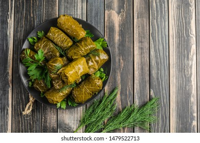 Delicious stuffed grape leaves (traditional doom Mediterranean cuisine Dolma) on a black plate with fresh cilantro and dill on dark wooden background top view with copyspace