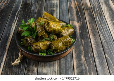 Delicious stuffed grape leaves (traditional doom Mediterranean cuisine Dolma) on a black plate with fresh cilantro and dill on dark wooden background side view with copyspace