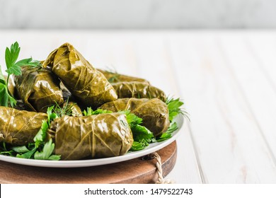 Delicious stuffed grape leaves (traditional doom Mediterranean cuisine Dolma) on a black plate with fresh cilantro and dill on a light wooden background side view closeup with copyspace