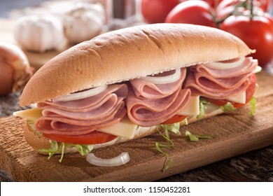 A delicious submarine sandwich with deli meats, lettuce, tomato, onion and cheese on a sub bun.