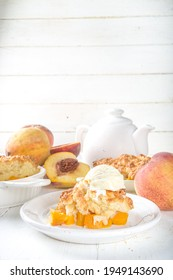 Delicious Summer Peach Cobbler, Homemade sweet summer pie with peaches and vanilla ice cream on white wooden background copy space