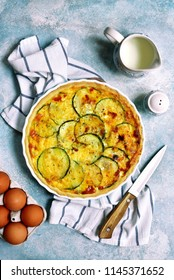 Delicious summer quiche with zucchini in a baking dish over light blue slate, stone or concrete background.Top view.