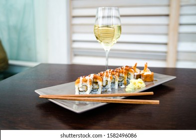 Delicious sushi served on a plate with white wine