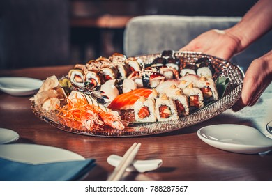 Delicious sushi set fresh made sashimi, nigiri and sushi rolls served on the exquisite plate in the luxurious restaurant. Traditional Japanese dish. Healthy organic food.