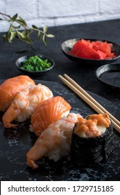 Delicious sushi set served on dark stone slate. Black background