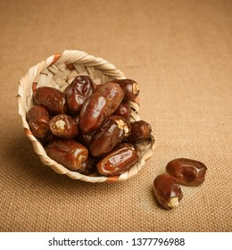 Delicious and sweet African Dates stored in a bowl made with palm leaves. Ripened dates served in an eco- friendly basket on jute background.