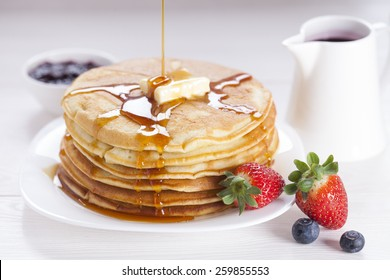 Delicious sweet American pancakes on a plate with fresh fruits and addons.