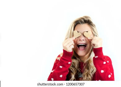delicious sweet biscuit cookies in the hands of a very beautiful bright young cheerful girl smiling and laughing in a Christmas sweater on a white isolated background in the studio