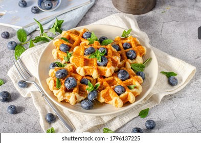 Delicious sweet breakfast, cripsy waffles, fresh berries and maple syrup
