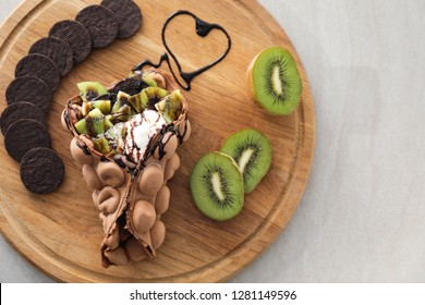 Delicious sweet bubble waffle on wooden board