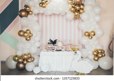 Delicious sweet buffet with cake. White swan Candy Bar. Design of balloons. Many white and golden balloons decorated wall