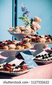 Delicious sweet buffet with cupcakes, berries, macaroons and other desserts. Wedding or Event decoration table setup in blue colors. Outdoors, summer time. Luxurious catering concept