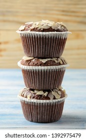 Delicious, sweet chocolate muffins, with almond petals on a blue wooden table.